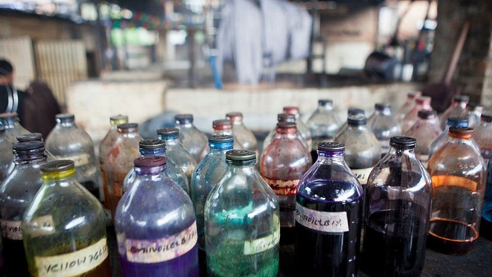 A collection of glass bottles containing dyes to be used for staining wool at a textile factory in Nepal
