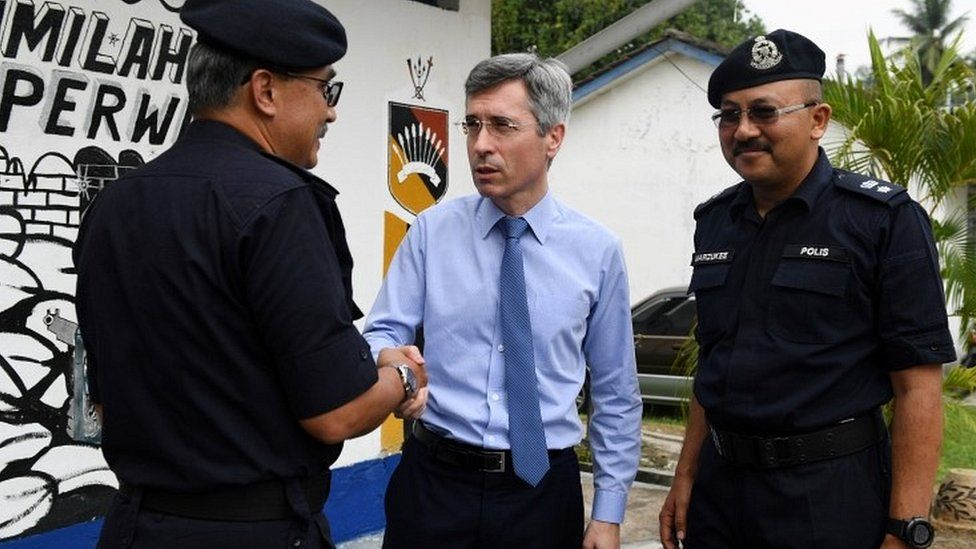 France's ambassador to Malaysia Frederic Laplanche with police officers