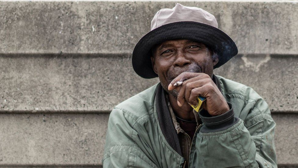 Lesotho miner Francis Malise, 60, smokes in the yard of the Kroondal Circle Labour Hostel, in Rustenburg on April 25, 2017.