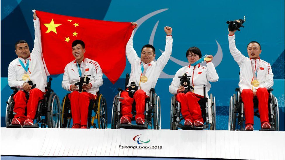 Curling competitors line up with their gold medal whilst waving a Chinese flag.