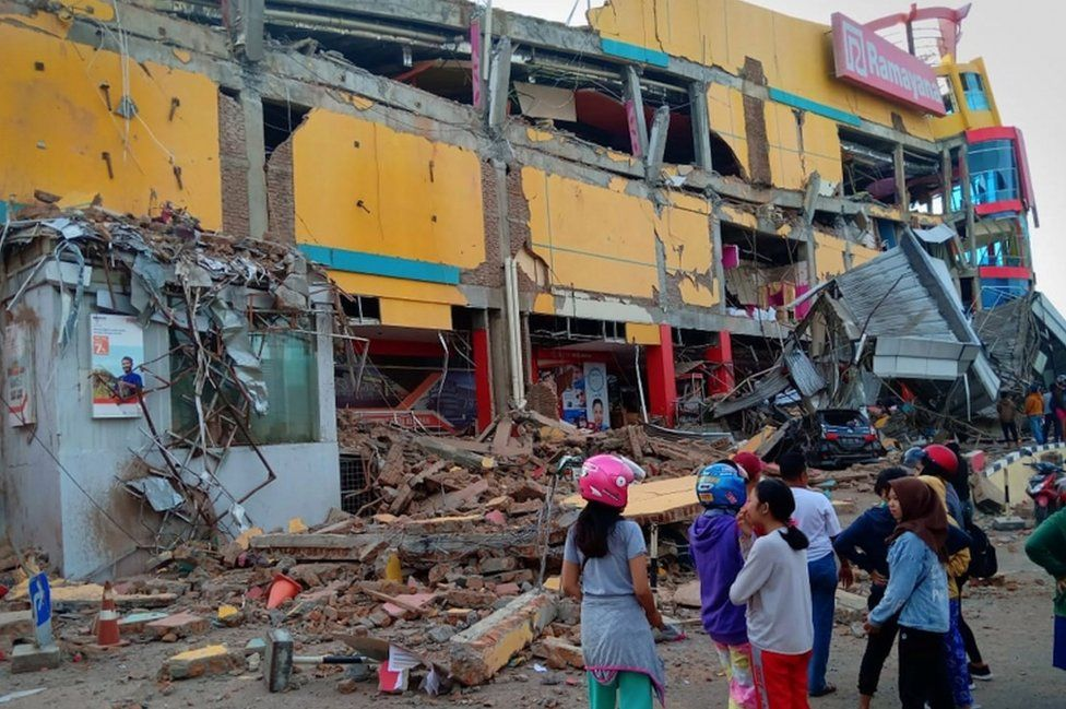 People stand in front of a damaged shopping mall after an earthquake hit the city of Palu, on Indonesia's Sulawesi Island