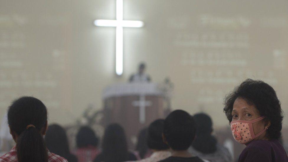 A woman wearing a mask attends Sunday church service in Palangkaraya, Indonesia