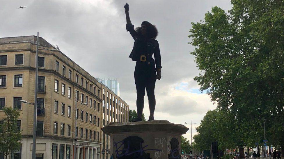 Jen Reid standing on plinth