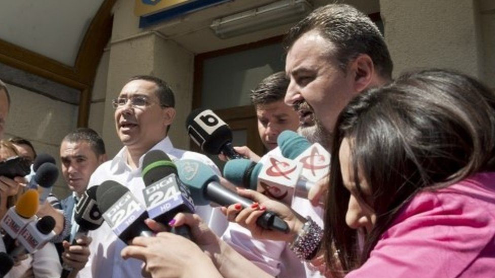 Romanian Premier Victor Ponta is surrounded by media as he exits the national anti-corruption prosecutors office (13 July 2015)