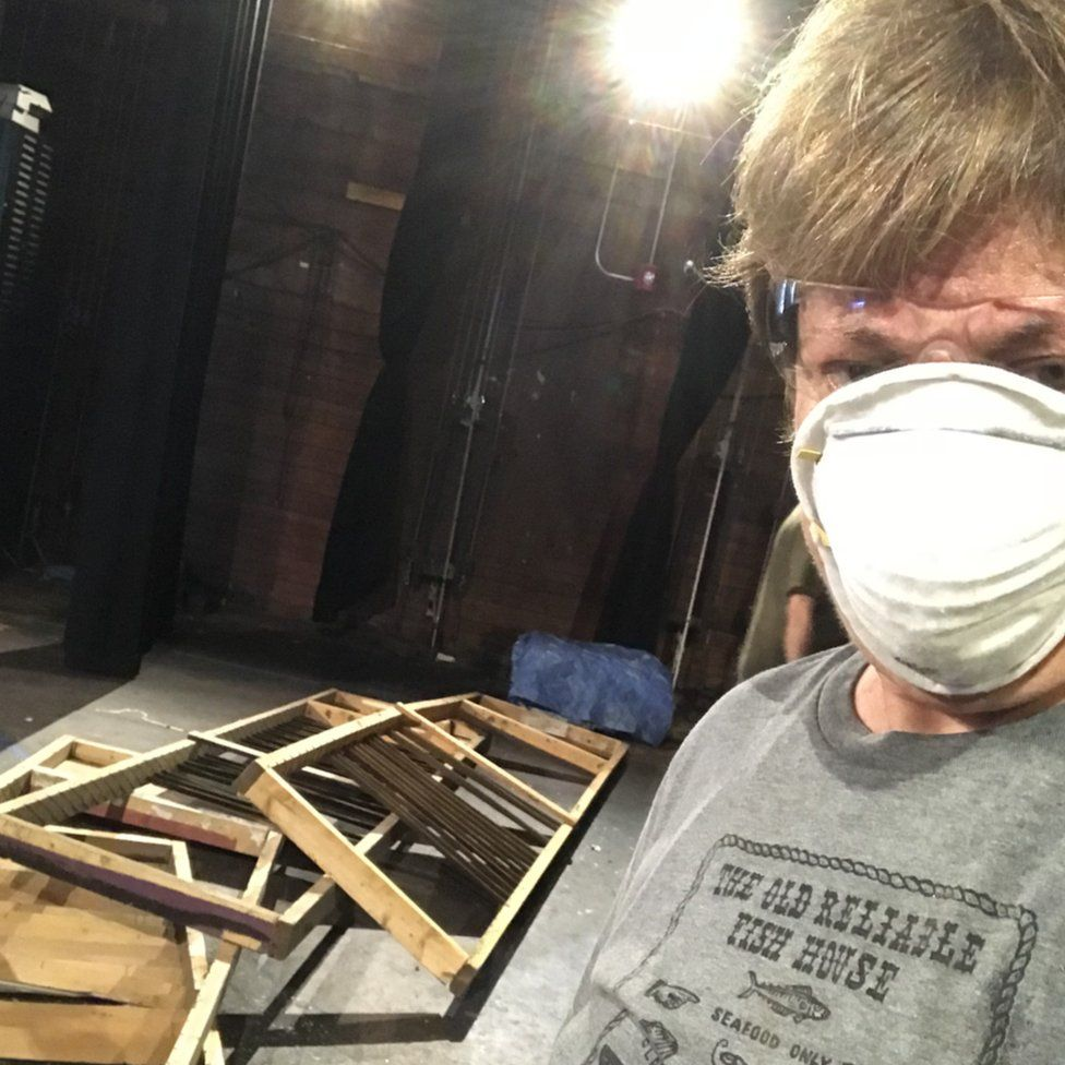 Rhea Becker wearing a mask while posing in front of broken up pieces of furniture