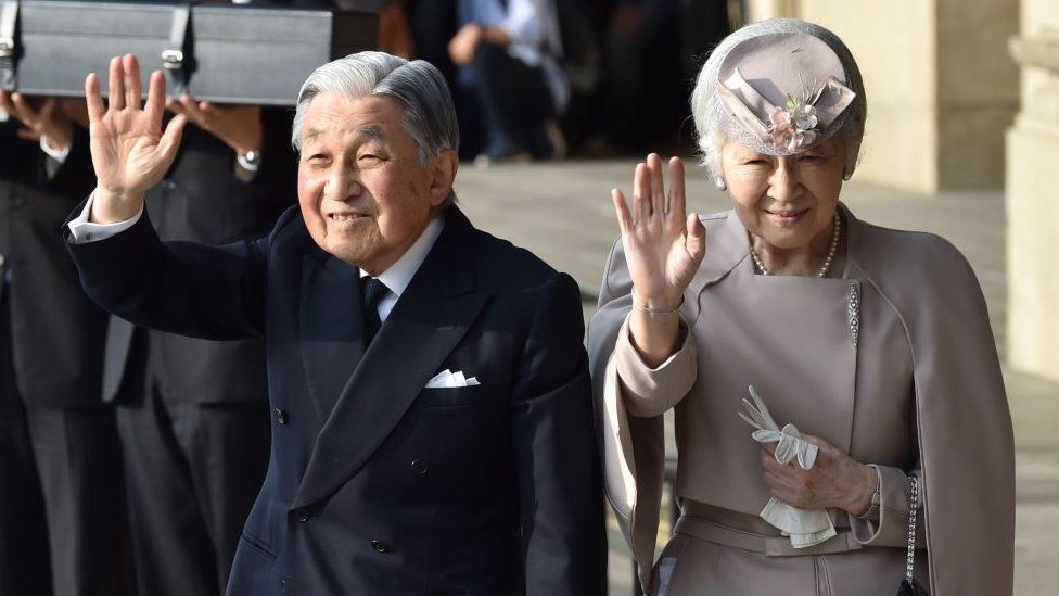 The then Emperor Akihito (L) and Empress Michiko (R) wave to well-wishers