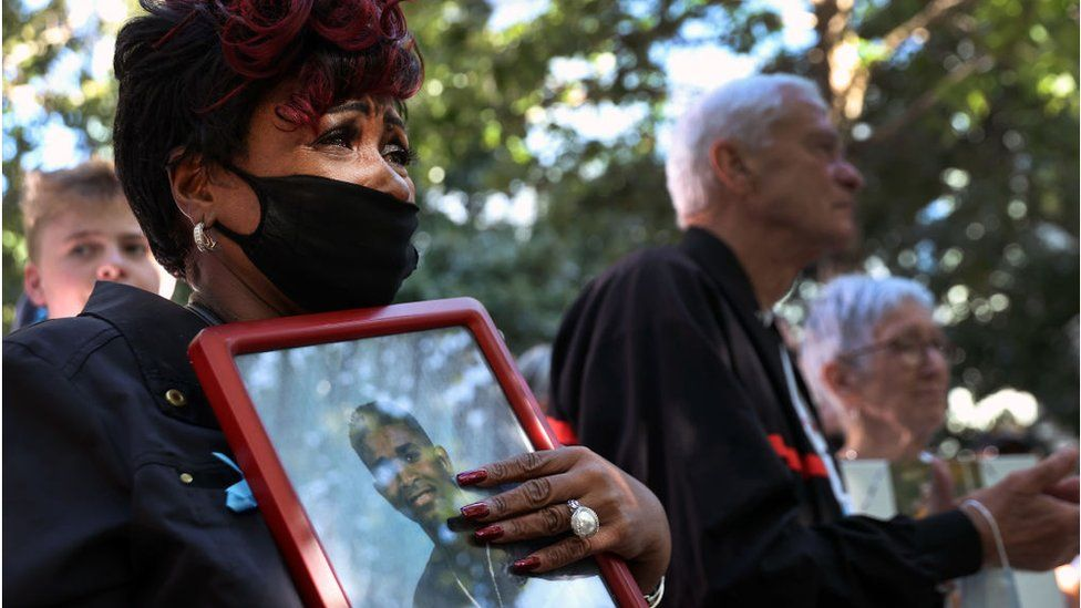 A woman crying holds a photo of a loved one