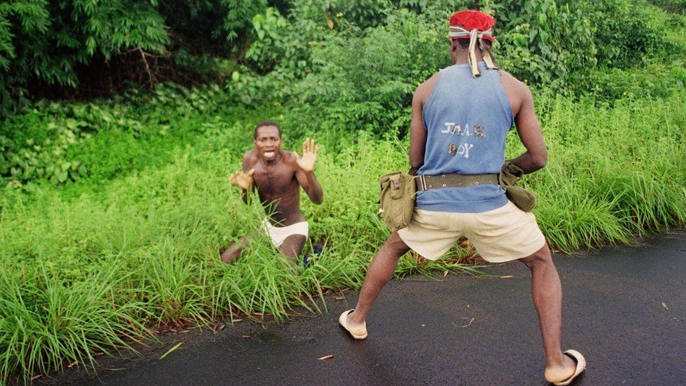 Gunman confronts a man during Liberia's civil war