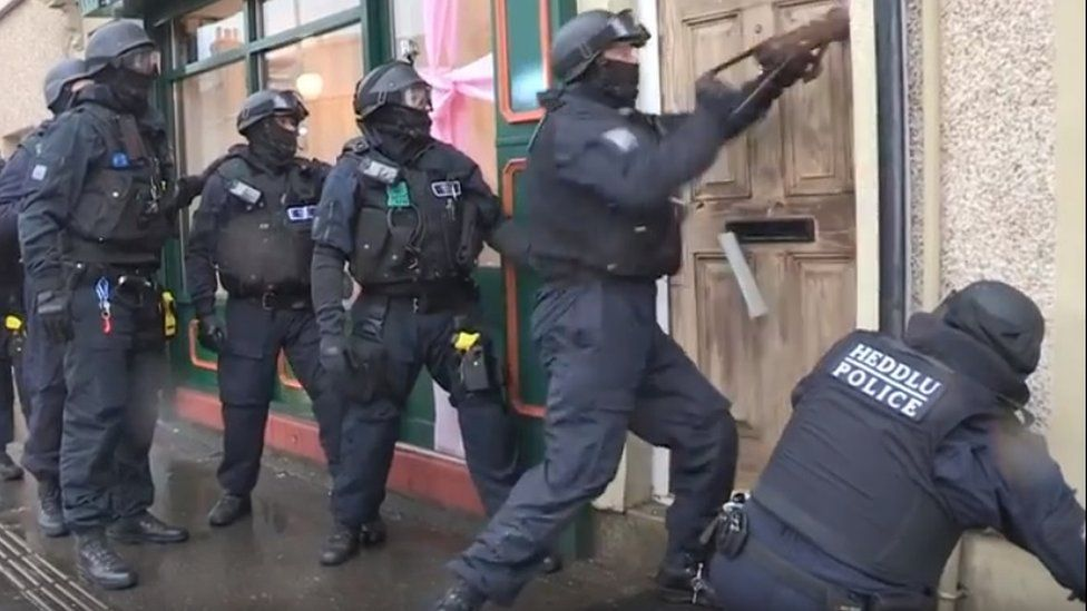 Police carrying out one of several raids in south Wales