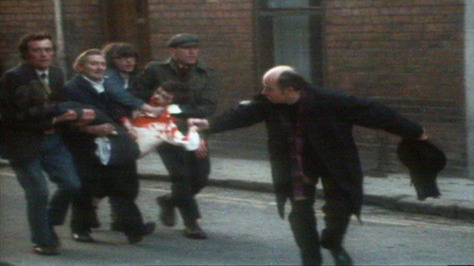 A priest waves a bloodstained handkerchief as four men carry an injured, bloodied man through the streets of Londonderry on Bloody Sunday