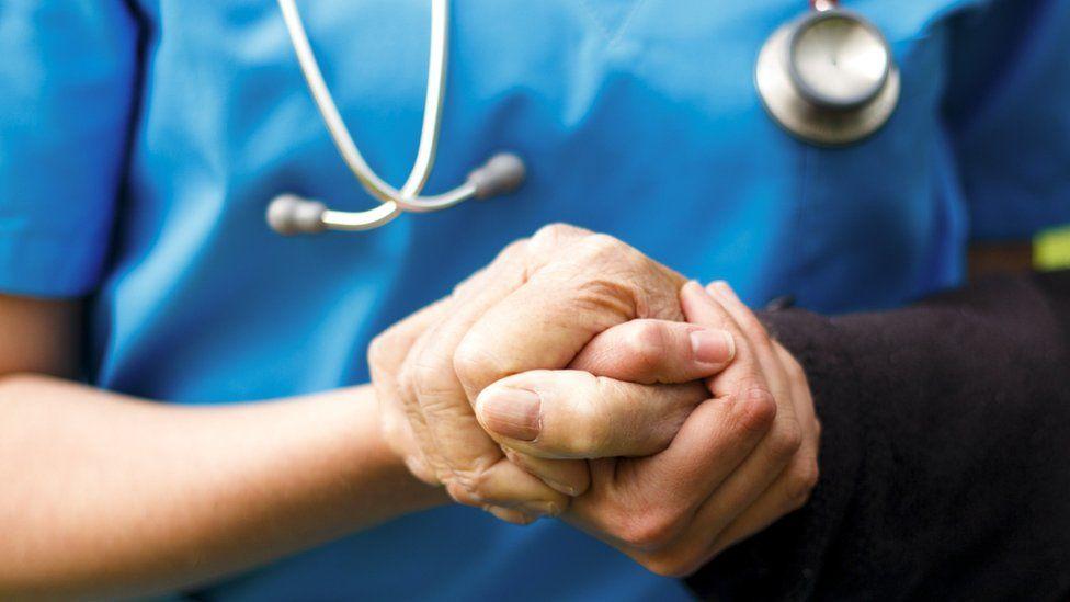 Nurse holding old man's hand