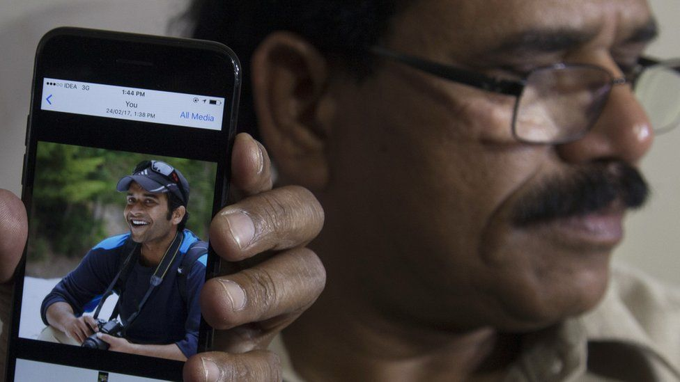 A picture of Alok Madasani is shown on a mobile phone as his father, Jaganmohan Reddy, talks to the media in Hyderabad, India, Friday, Feb. 24, 2017