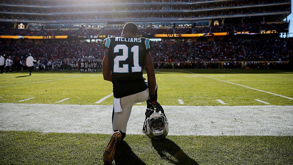 Teddy Williams of the Carolina Panthers kneels