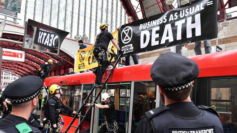 Police prepare to remove climate change activists on the roof of a DLR train at Canary Wharf station