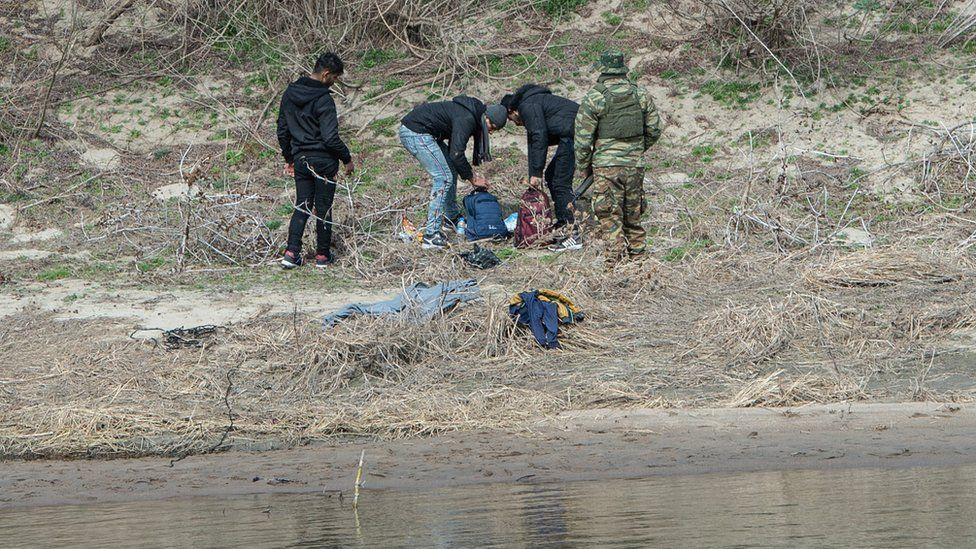 Border guards detain migrants in Edirne on the Greek shoreline of the Evros river after they crossed from Turkey to Greece, 4 March
