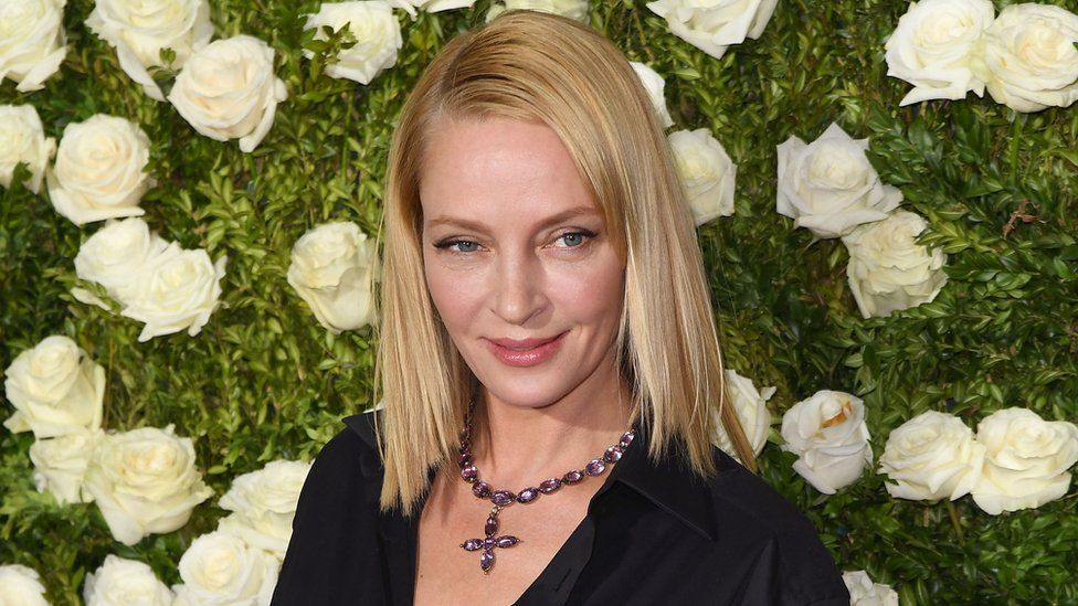 Uma Thurman in June 2017, photographed in front of a wall of white roses