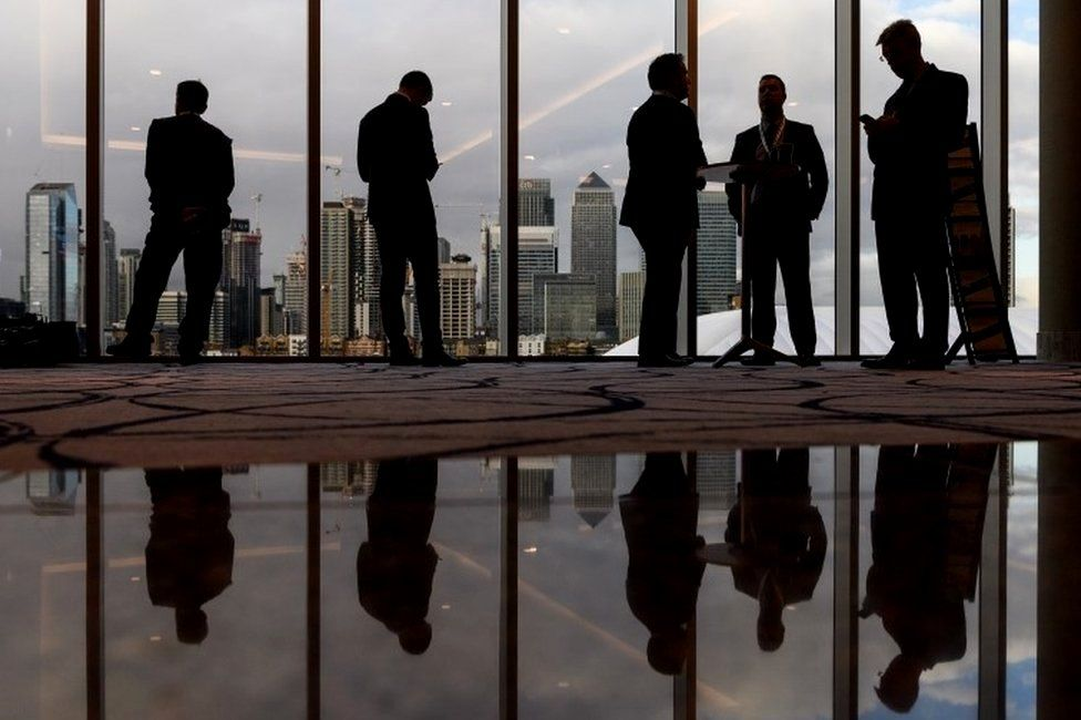 Business people with Canary Wharf in background