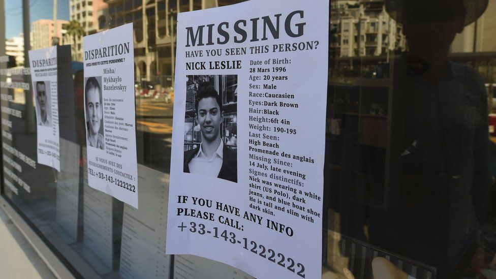 A man looks at missing person notice in Nice with picture of Nicolas Leslie on 16 July