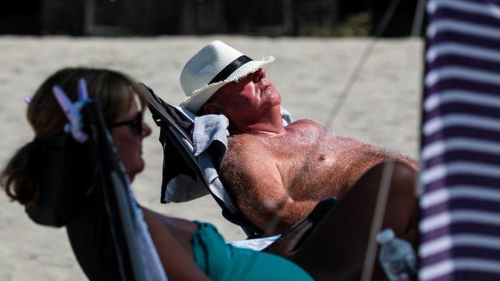 man sunbathes on beach in Chichester
