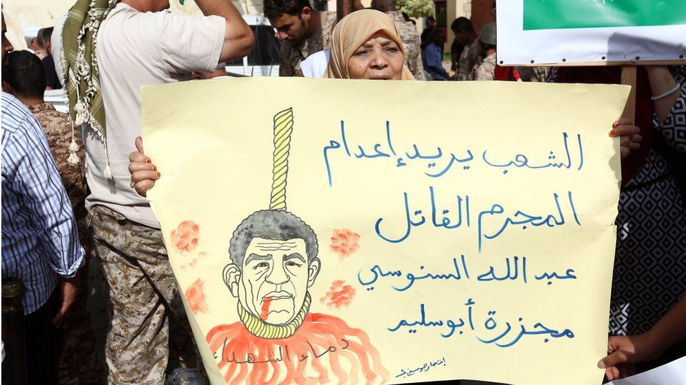 A Libyan woman holds a poster reading in Arabic: 'The people want the death penalty for Abdullah Senussi for the Abu Salim massacre' as they demonstrate outside a court against the ex-intelligence chief