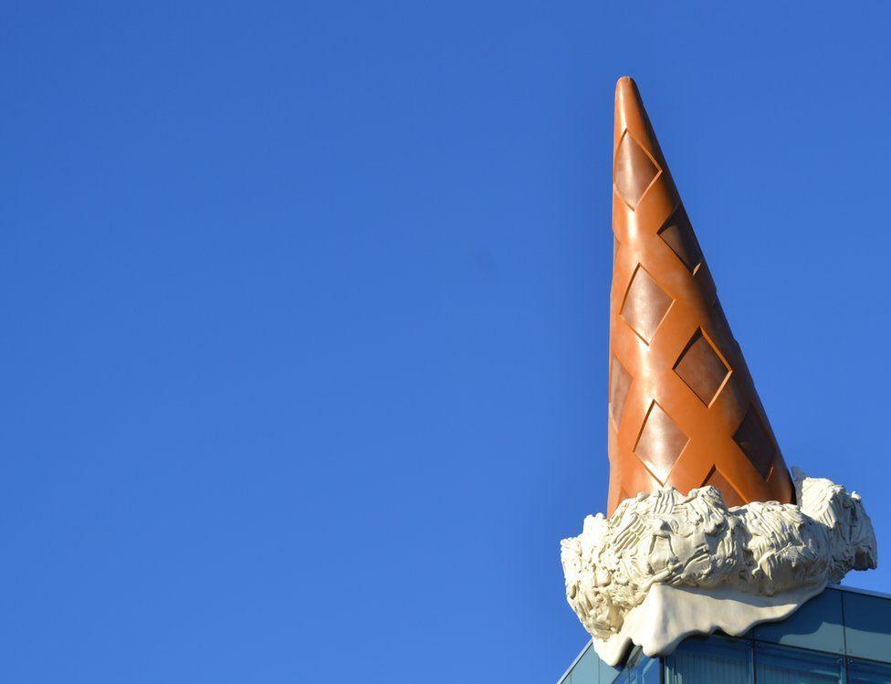 An ice cream cone against a bright blue sky