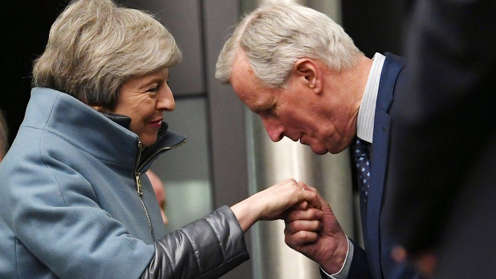 European Union chief Brexit negotiator Michel Barnier (R) kisses the hand British Prime Minister Theresa May (L)