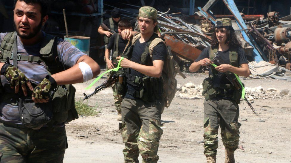 Free Syrian Army fighters walk with their weapons in Ramousah area southwest of Aleppo