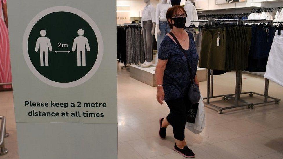 Woman wearing face mask in London shop