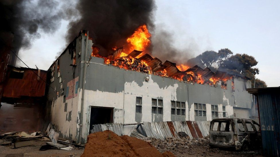 A business is set on fire during widespread looting and protests in Durban, South Africa - 12 July 2021