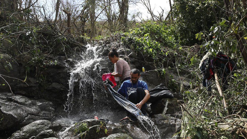 A couple washes their clothing in a stream on Sunday