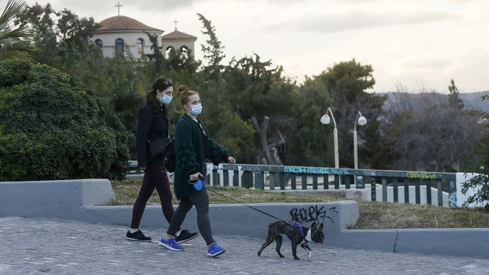 People wearing face masks walk their dog in Athens, Greece
