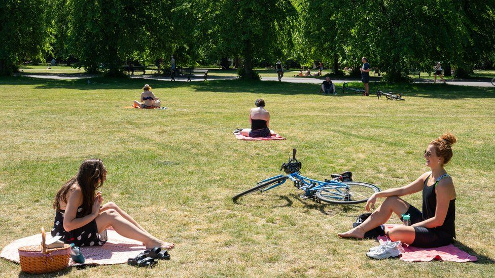 Two women observe social distancing whilst enjoying the hot weather in Greenwich Park, London, 20 May, 2020