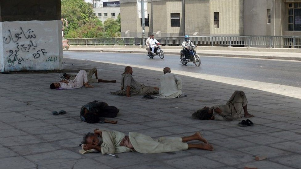 Pakistani men rest under a bridge during a heatwave in Karachi on June 29, 2015.