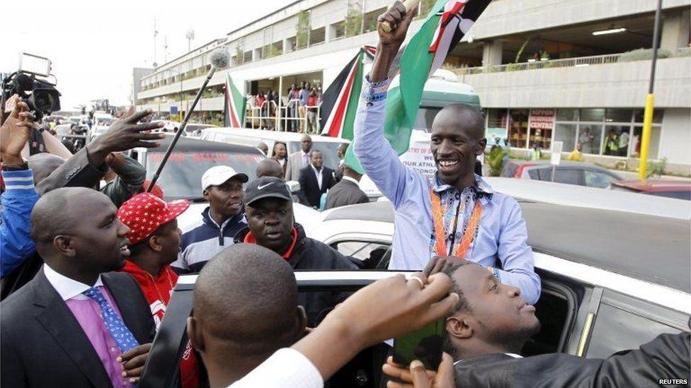IAAF men's 3000 metres steeplechase gold medallist Kemboi greets his supporters at the Jomo Kenyatta airport Nairobi, Kenya