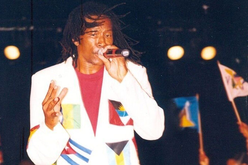 King Onyan performs wearing a flag-covered white suit