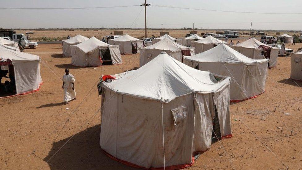 Sudanese displaced following heaving floods, walk at a newly established camp near Wad Ramli, some 45 km north of Khartoum, Sudan, 25 August 2019.