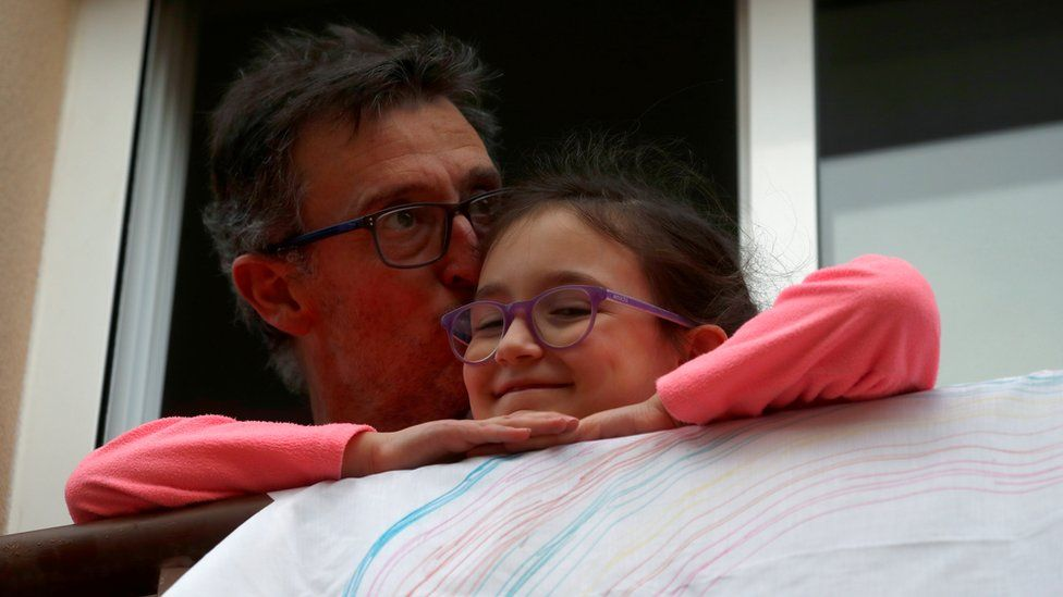 A man kisses his daughter after applauding in support of health workers