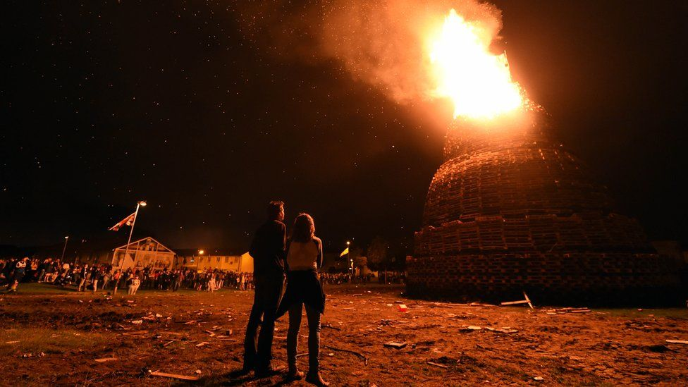 People watch the bonfire at Hopewell Square in Belfast's Shankill area