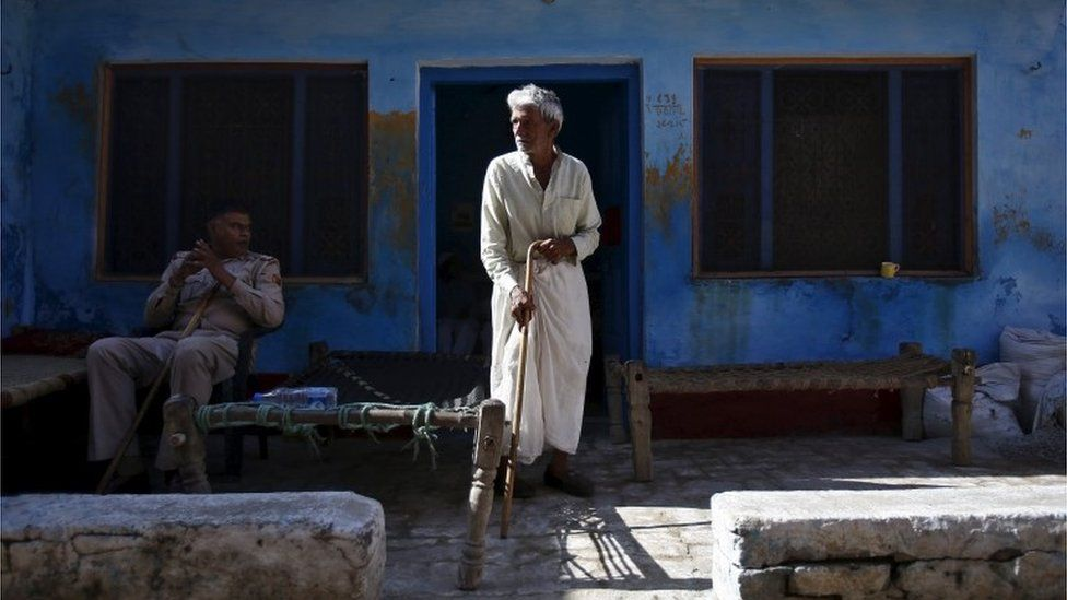"A policeman sits near a relative of Akhalaq Saifi, who was killed by a mob, outside Saifi""s house at Bisara village in Uttar Pradesh, India, October 2, 2015."