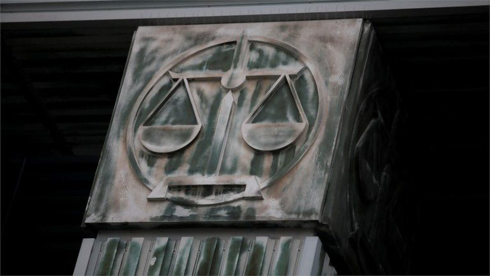 An image of scales is pictured on a pillar of the Supreme Court in Warsaw
