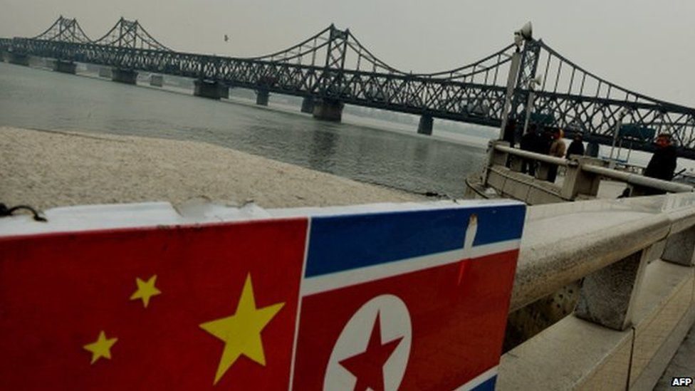 The Chinese and North Korean flags attached to a railing as trucks carrying Chinese-made goods cross into North Korea on the Sino-Korean Friendship Bridge at the Chinese border town of Dandong