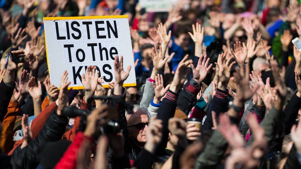 People hold their hands up as directed by musician Brandi Carlile at Seattle Center during the March for Our Lives rally