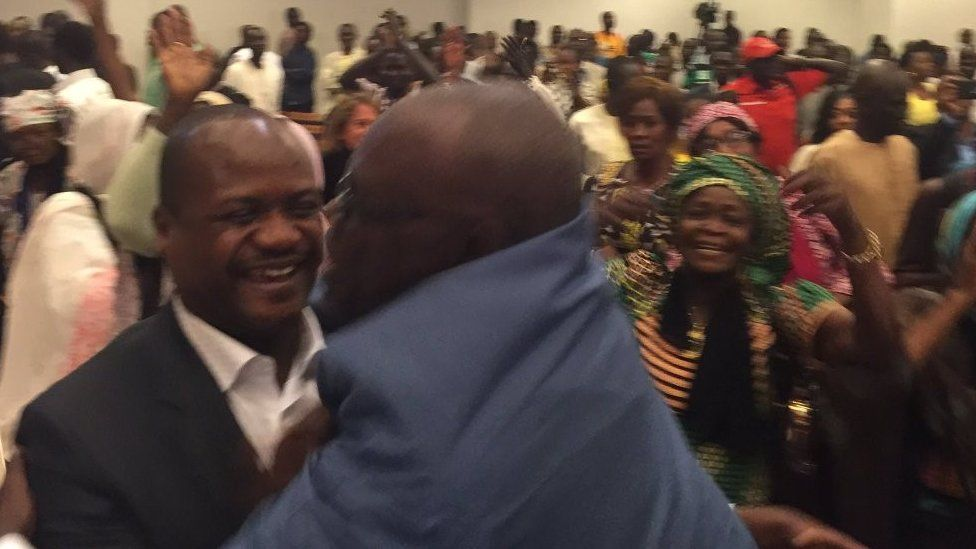 Two men hug each other while others cheer behind them in the courtroom