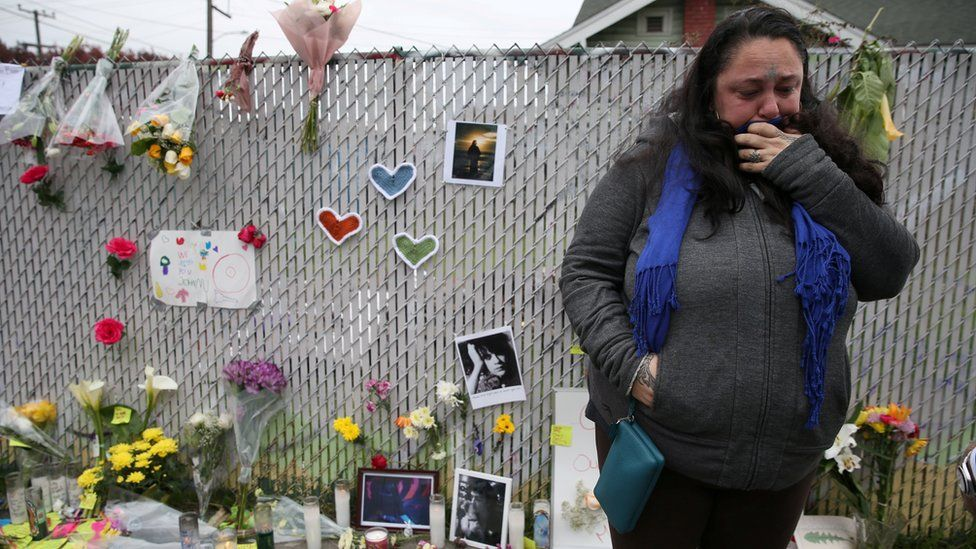 A mourner cries at a memorial near the burned warehouse in December 2016