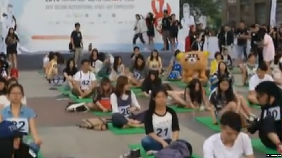 Contestants sitting on floor mats during the competition