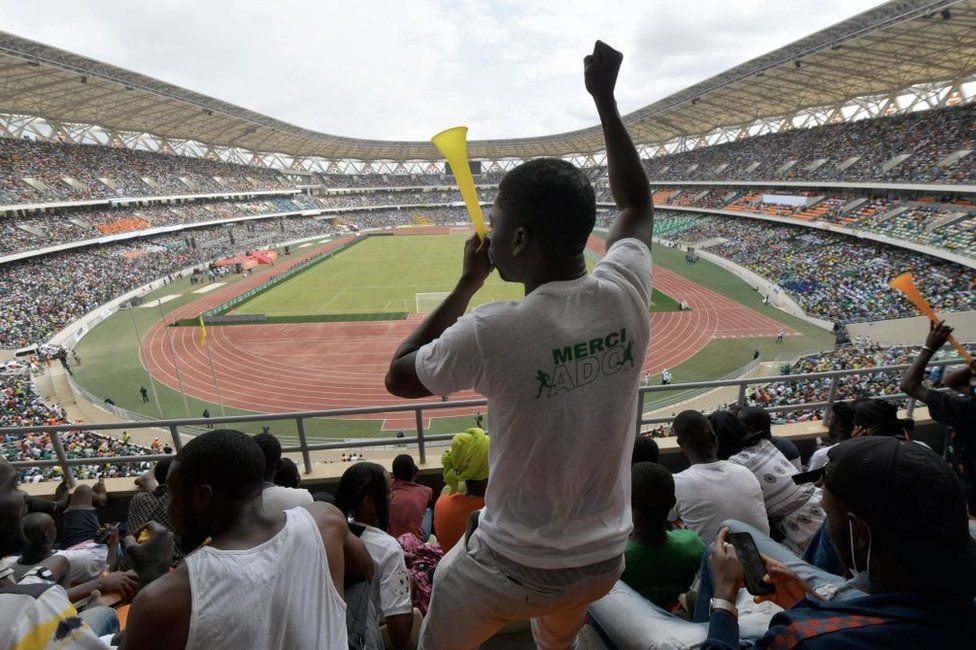 A man blows a vuvuzela during the inauguration ceremony of Ivory Coast's new 60,000-seat Olympic stadium, built with the help of China, in Ebimpe, outside Abidjan, on October 3, 2020 ahead of 2023 Africa Cup of Nations.