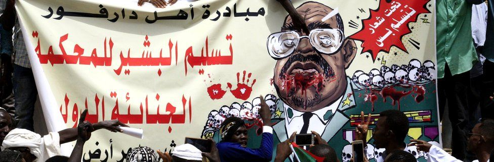 "Sudanese protesters hold up a banner depicting ousted president Omar al-Bashir with text in Arabic reading: ""Darfur people's initiative: handing over al-Bashir to the International Criminal Court (ICC)"", in the capital Khartoum, 19 April 2019"