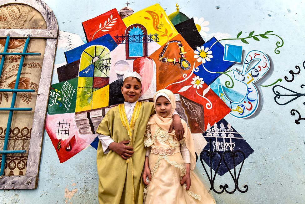 Children pose in front of street art depicting cultural elements including mosques, and old window lattices of the old town of Iraq's northern city of Mosul