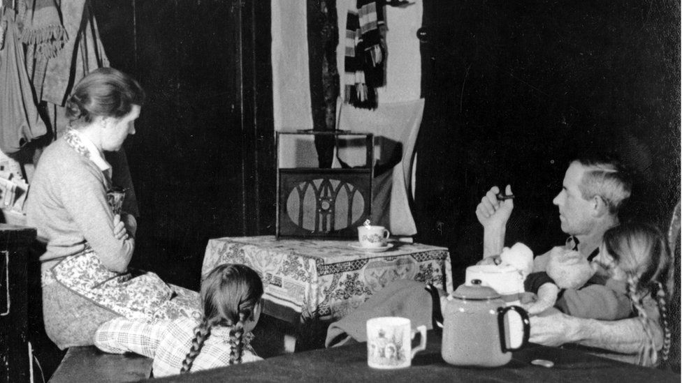 a family around a wireless radio, listening to the news