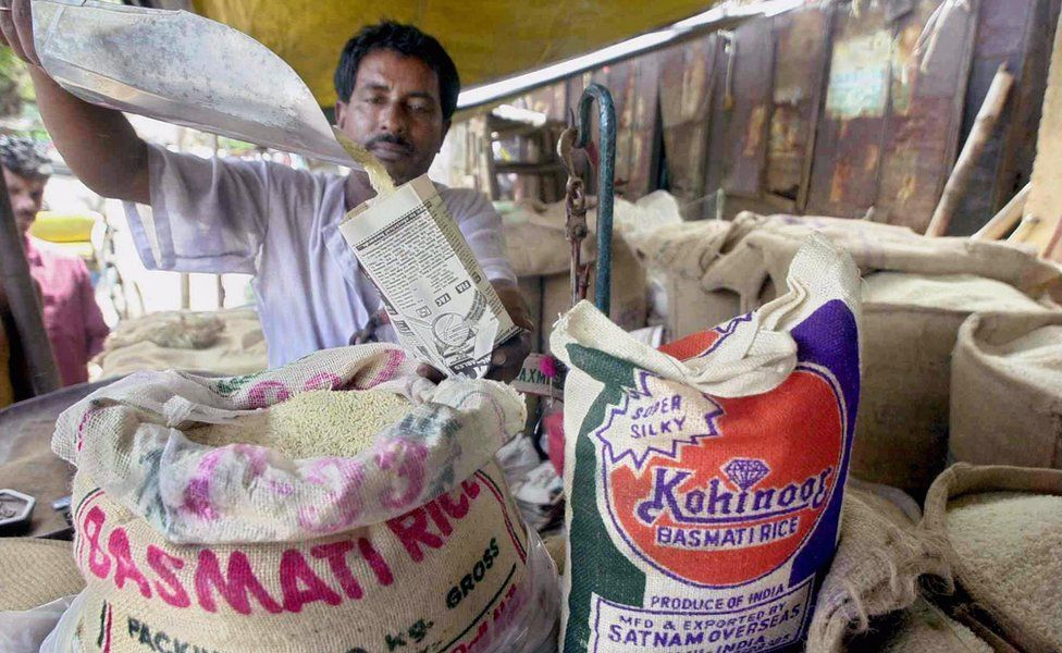 A rice vendor fills a small paper packet with Basmati rice in Calcutta